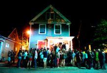 ludzie przed domem jednorodzinnym wyglądającym na imprezę