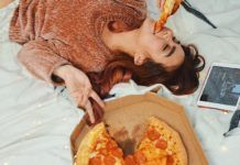 Dziewczyna leżąca na łóżku z pizzą