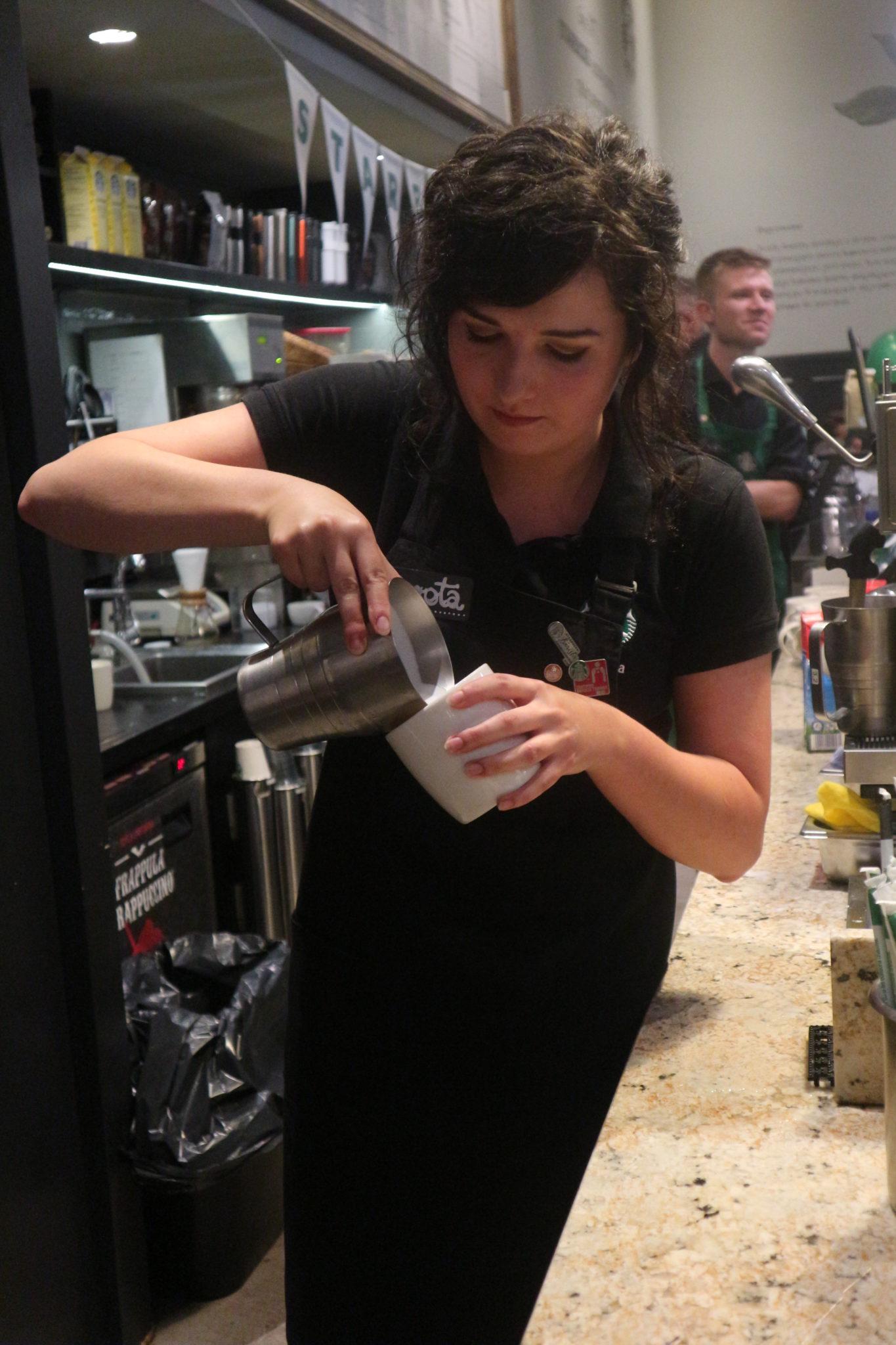 Kobieta nalewająca mleko do kawy