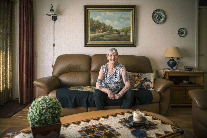 Starsza kobieta z tatuażami siedząca na kanapie