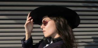 Dziewczyna w kapeluszu stojąca profilem