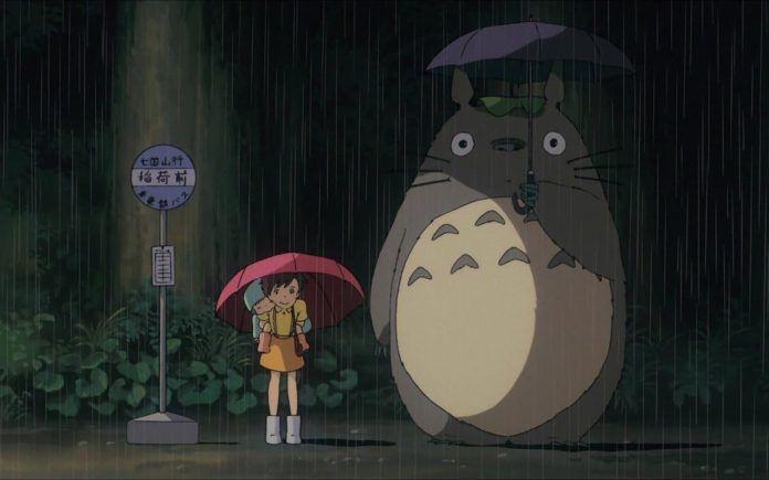 Na zdjęciu widać małą dziewczynkę w żółtej sukience trzymającą czerwony parasol. Jest deszczowa noc, a obok niej stoi duże, szare stworzenie z parasolem.