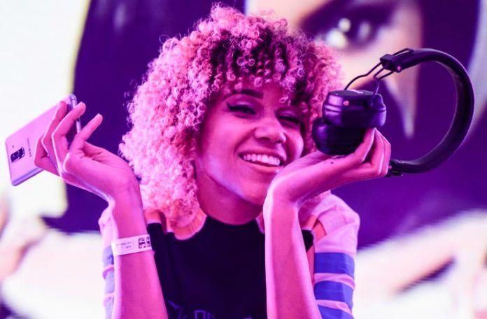 Uśmiechnięta dziewczyna trzymająca słuchawki i telefon w dłoni