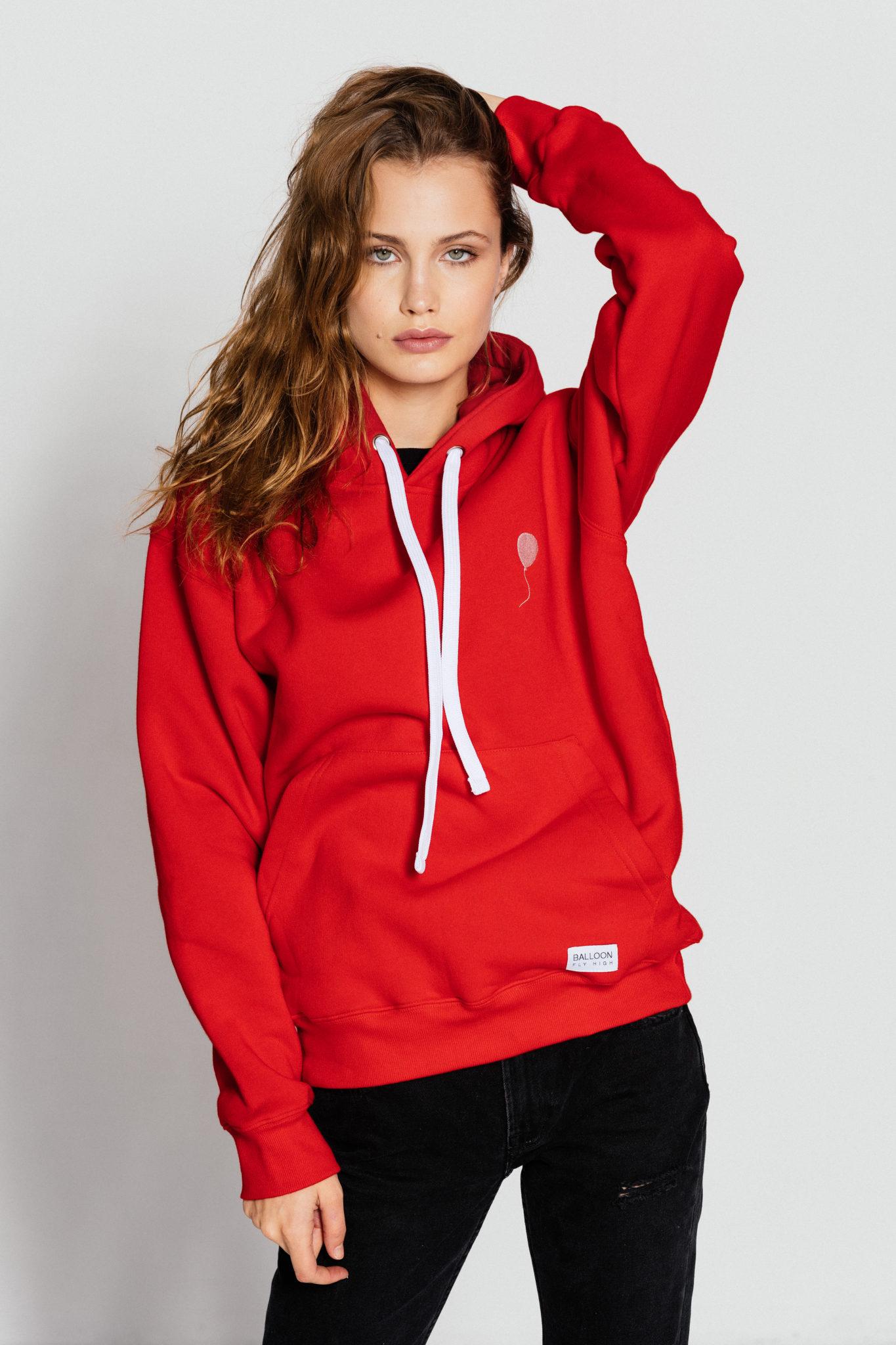 Na tle bialej sciany pozuje dziewczyna w czerwonej sportowej bluzie i czarnych spodniach