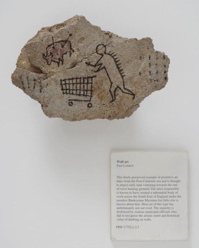 na zdjęciu znajduje się człowiek z wózkiem sklepowym na prehistorycznym kamieniu oraz biała tabliczka z podpisem