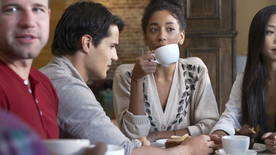 ludzie siedzący i pijący kawę