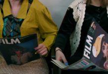 dwie dziewczyny czytające magazyny filmowe, jedna w żółtej marynarce, druga w czarnym swetrze, kadr ucina nogi i głowy