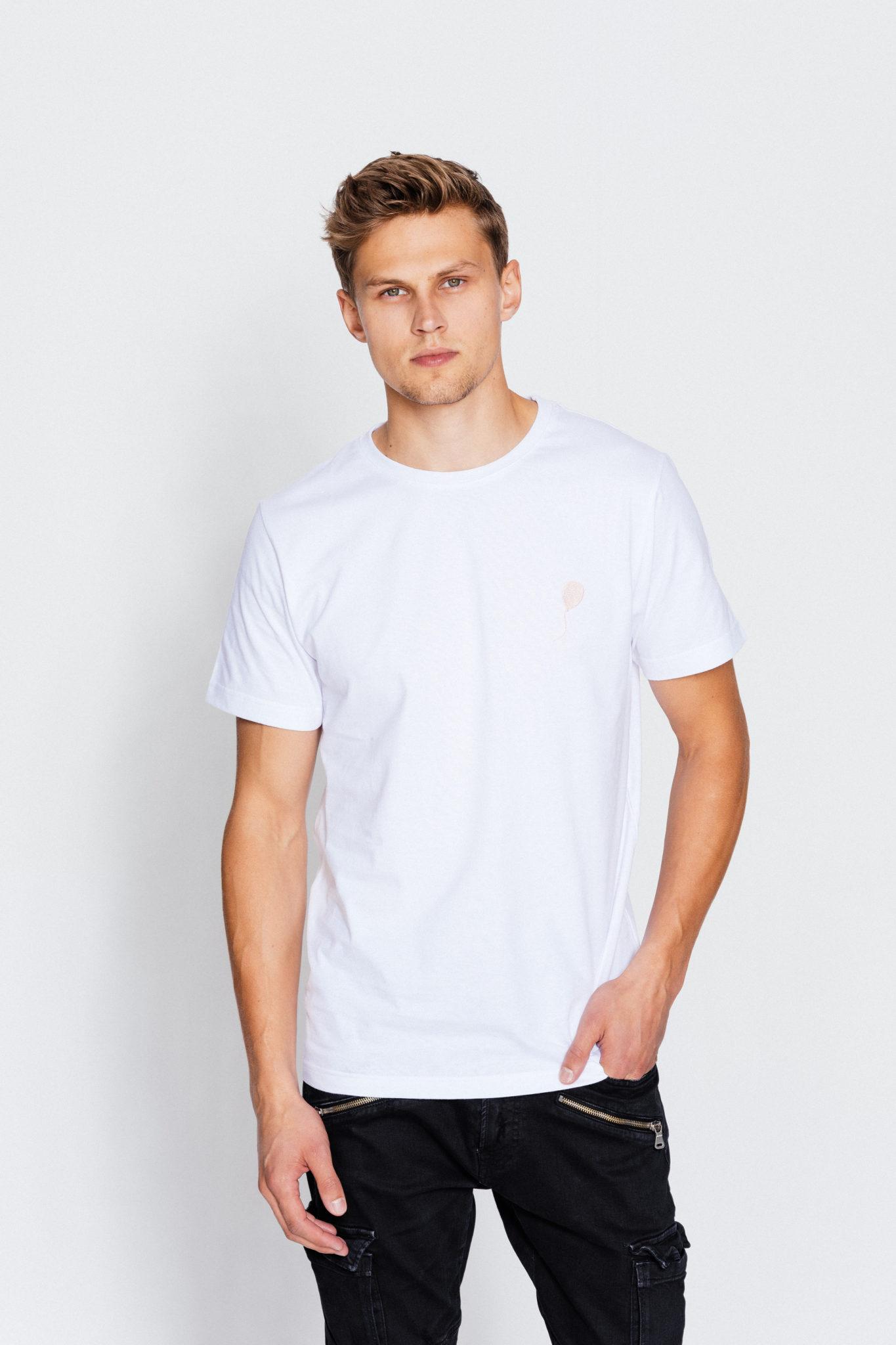 Na zdjeciu chlopak ubrany w bialy tshirt pozuje na tle bialej sciany