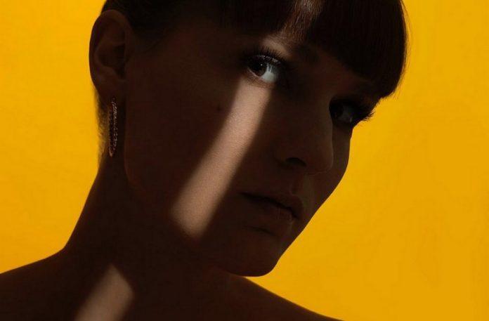 Zacieniona twarz dziewczyny na żółtym tle ze smugą światła na oku