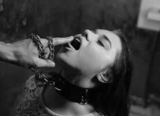 Czarno-białe zdjęcie przedstawiające dziewczynę w obroży