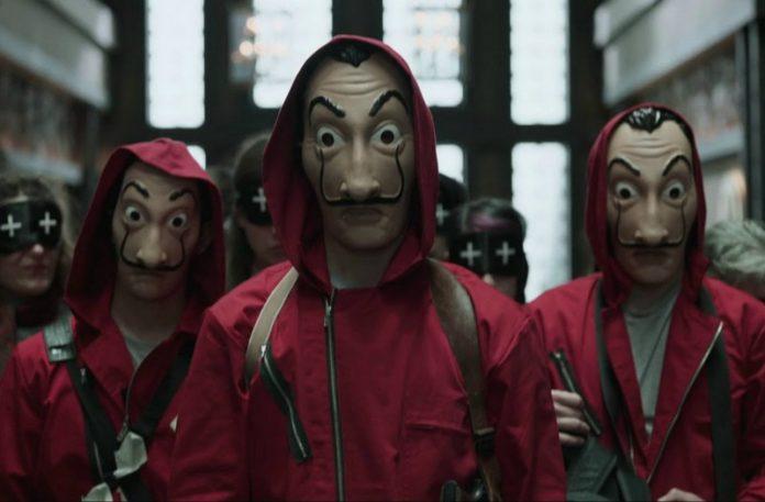 Ludzie ubrani w takie same maski i czerwone kombinezony