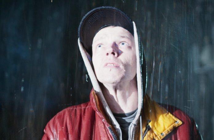 Mężczyzna w czerwonej kamizelce i czapce z daszkiem stojący w deszczu