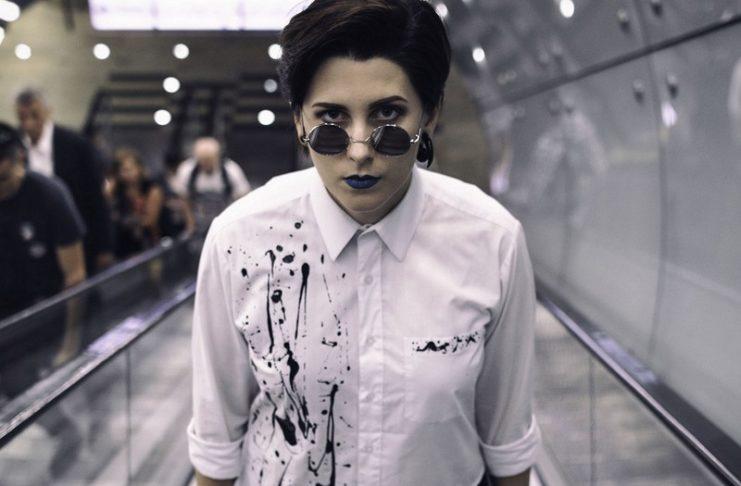 Dziewczyna w poplamionej koszuli i okularach na schodach metra
