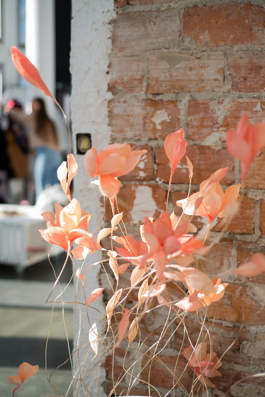 Na tle ceglanej sciany stoja pomaranczowe bibulkowe kwiaty