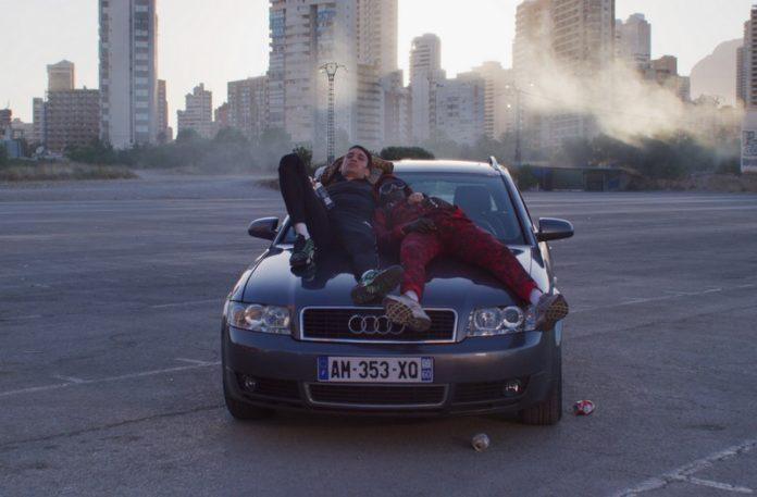 Dwoch ludzi lezacych na masce samochodu
