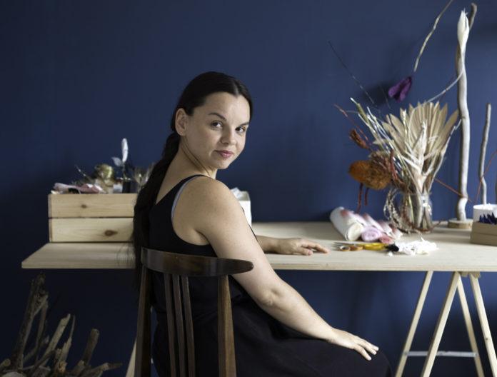 Na zdjeciu widzimy odwrocona plecami kobiete w upietych brazowych wlosach siedzi przy biurku pelnym bibulkowych kwiatow