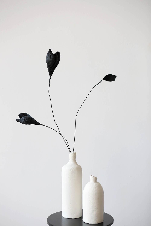 Na tle bialej sciany w bialym wazonie stoja trzy czarne bibulkowe kwiaty
