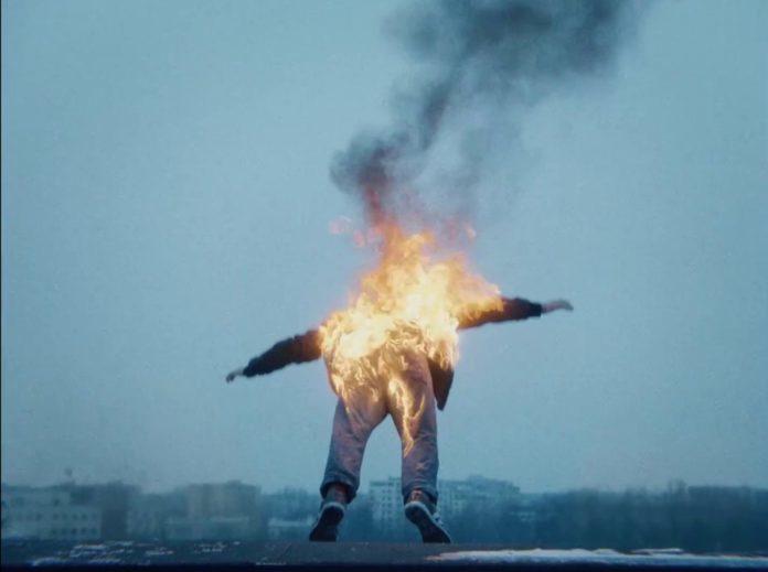 Mężczyzna w ogniu spadający z dachu