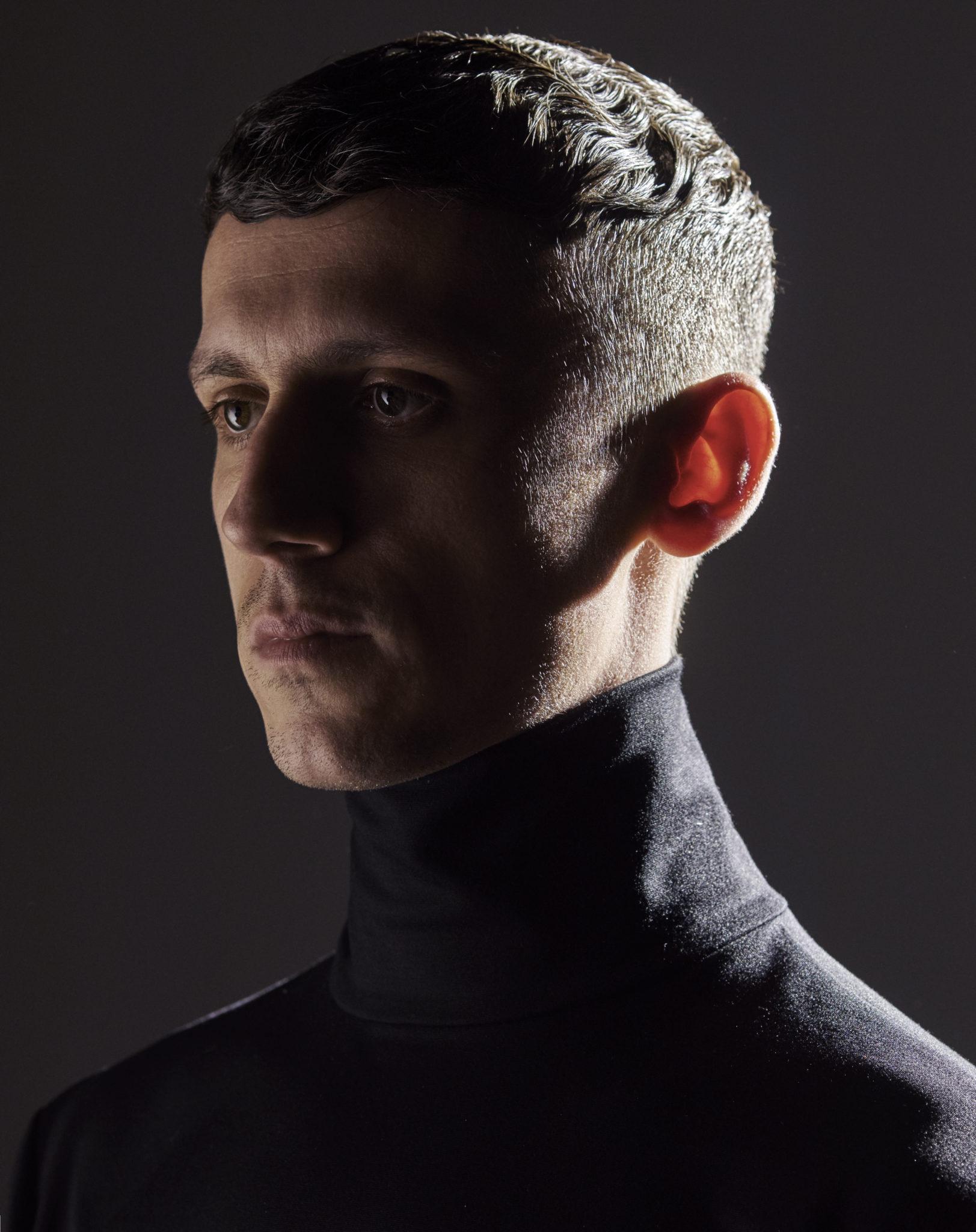 Ciemny profil mezczyzny ubranego w czarny golf na ciemnym tle