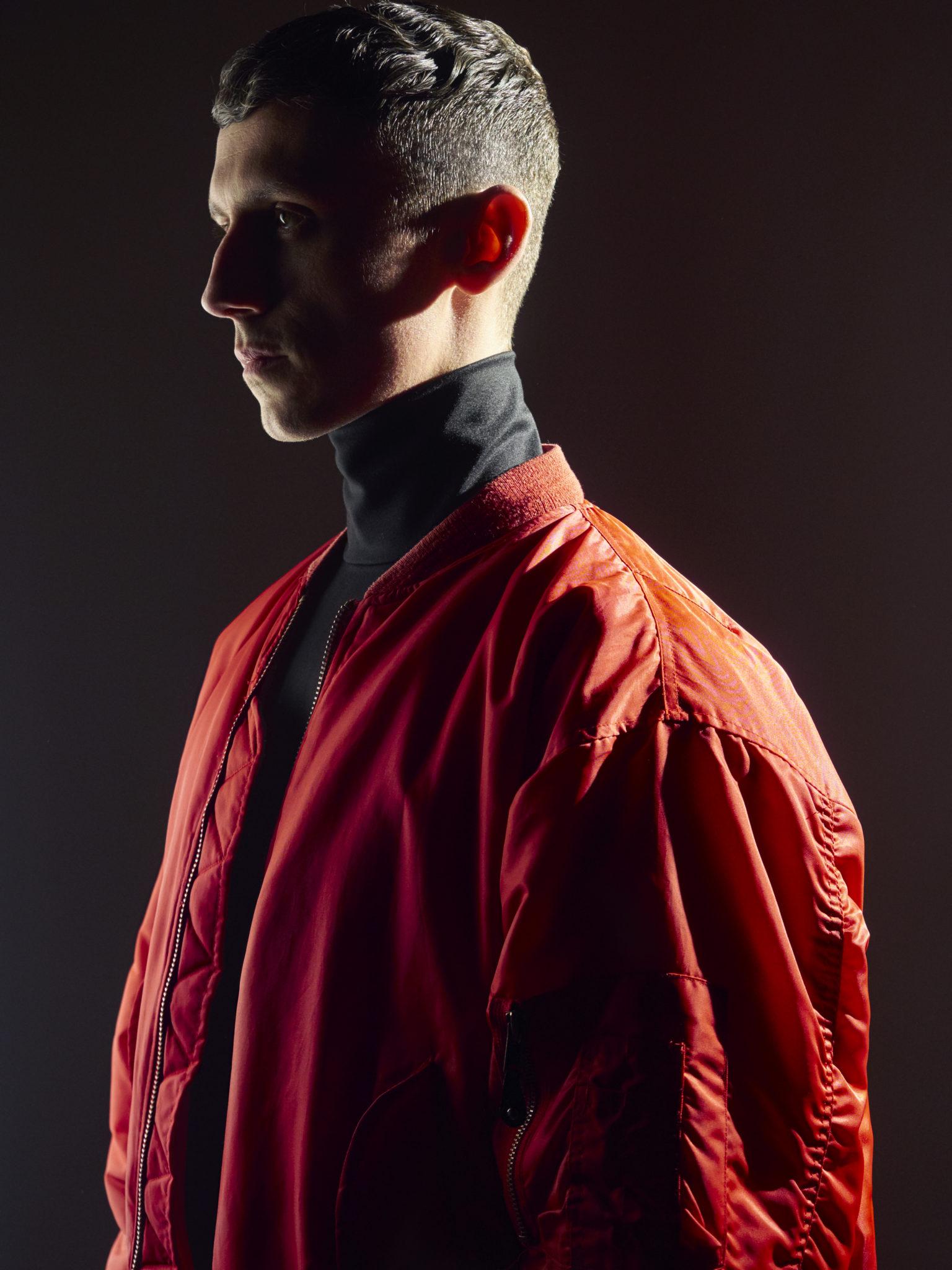 Ciemne zdjęcie mężczyzny ubranego w czerwoną bomberkę i siwy golf stojący profilem na ciemnym tle