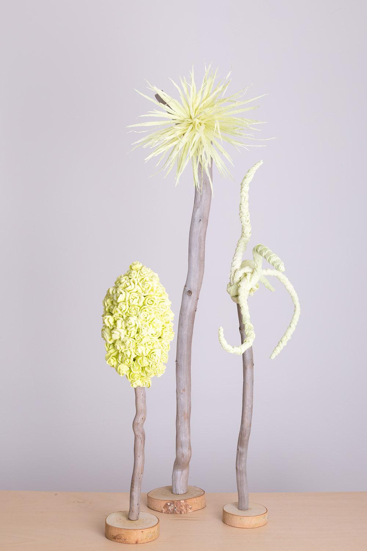 Na zdjeciu na tle szarej sciany stoja trzy pasetelowe rozki weselne wykonane z bibulkowych kwiatow
