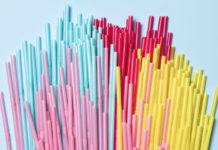 na błękitnym tle znajdują się plastikowe słomki koloru różowego, czerwonego, niebieskiego i żółtego