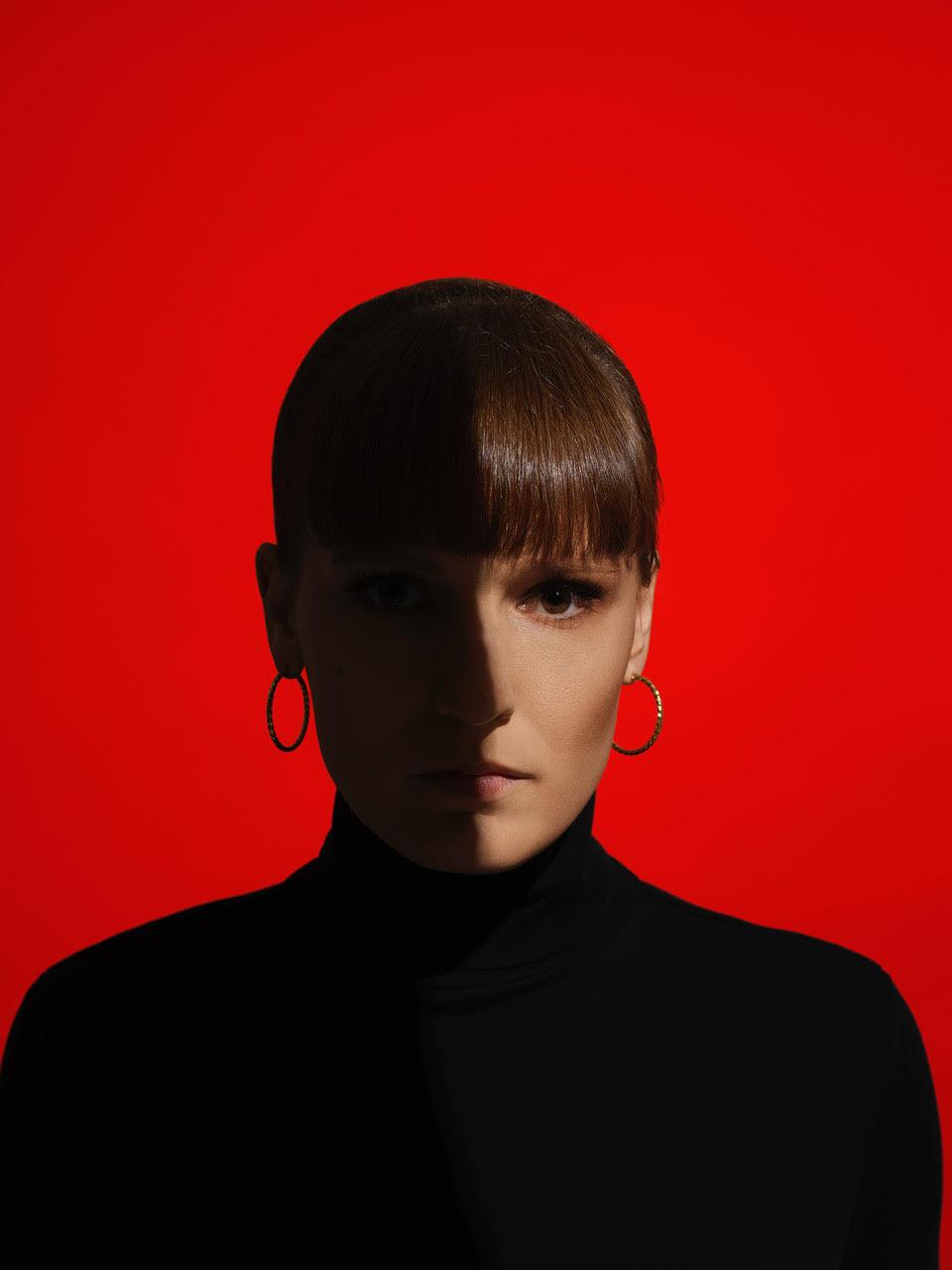 Na zdjeciu widzimy mloda kobiete w czarnym golfie portret na czerwonej scianie do polowy twarz oswietlona
