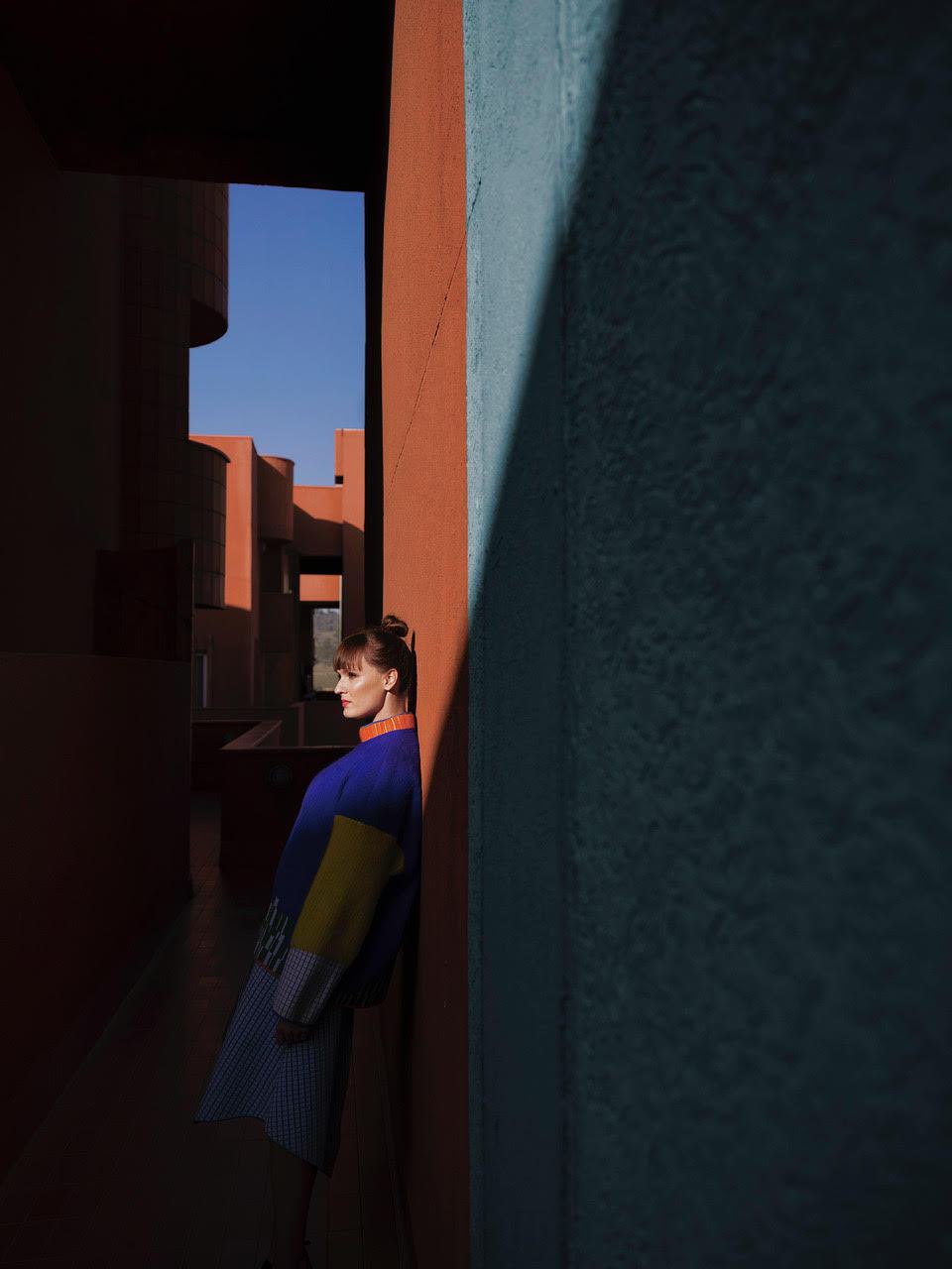 Mloda kobieta stoi bokiem na tle niebieskiego budynku
