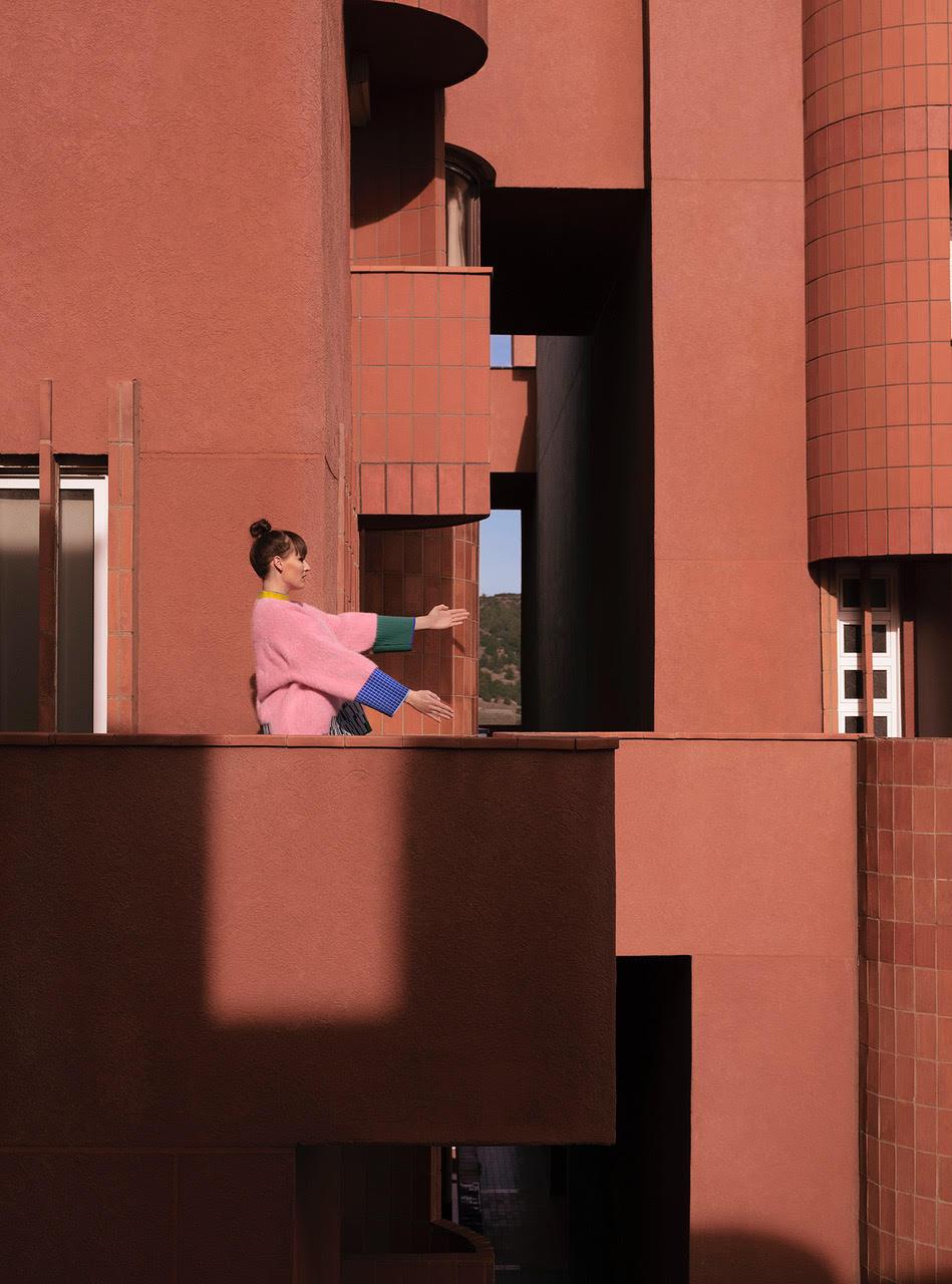 Mloda kobieta pozuje na tle rozowego budynku