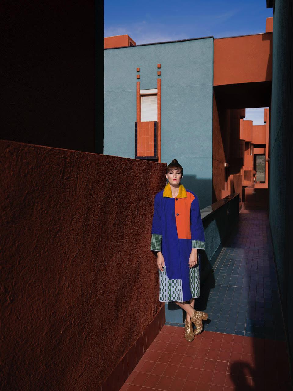 Mloda kobieta pozuje w kolorowej sukience na tle niebieskiego budynku