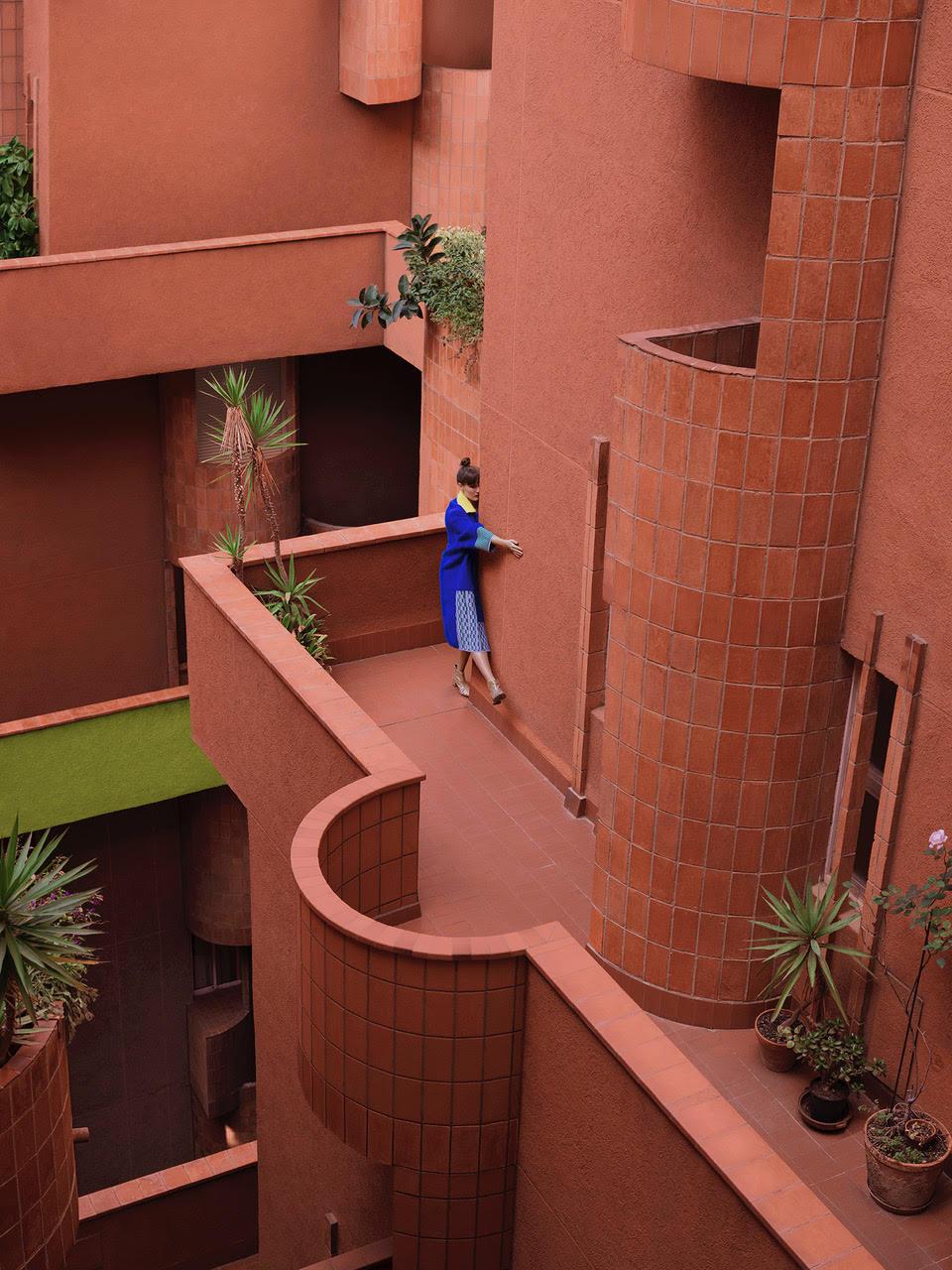Młoda kobieta pozujaca na zawilym rozowym budynku