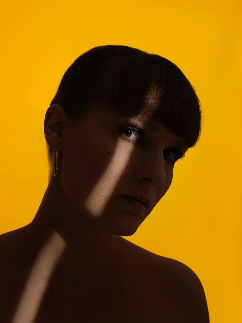portret mlodej kobiety do polowy twarz oswietlona na zoltym tle
