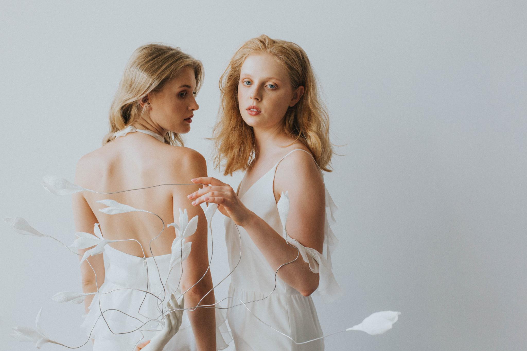 Na zdjeciu widzimy dwie delikatne modelki ubrane w biale zwiewne sukienki w rekach trzymaja biale bibulkowe kwiaty