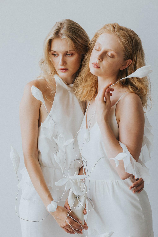 Dwie mlode delikatne dziewczyny ubrane w biale zwiewne sukienki w rekach trzymaja bibulkowe biale kwiaty