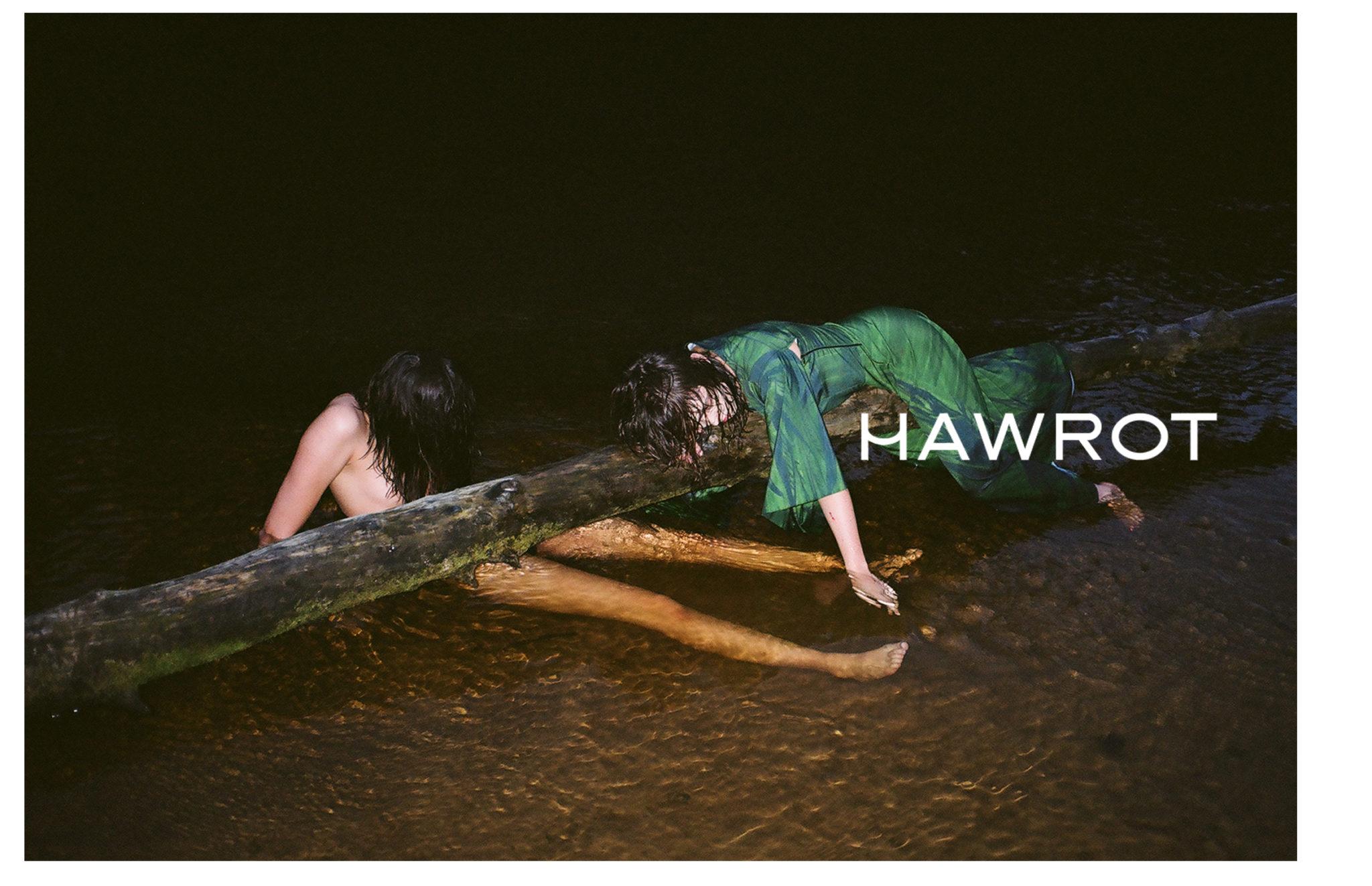 Na zdjeciu w nocy widzimy dwie mlode dziewczyny jedna lezy w wodzie druga lezy na pniu