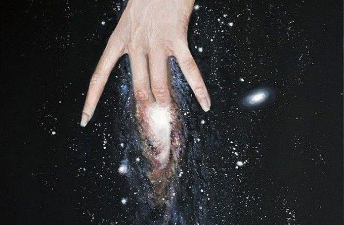 Dłoń kobiety na tle galaktyki