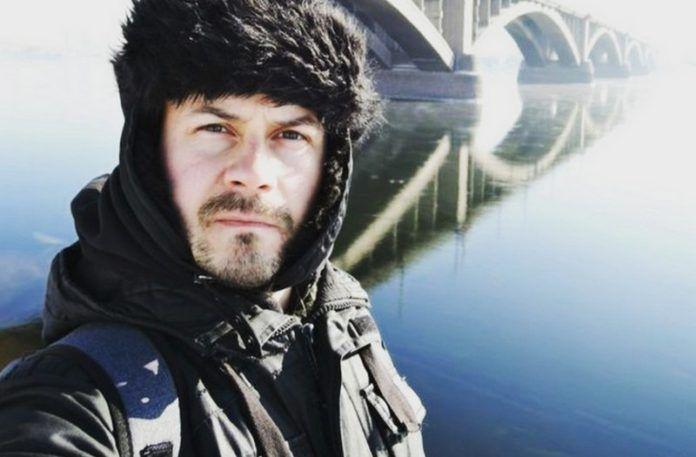 Mężczyzna ubrany w czapkę, w tle most