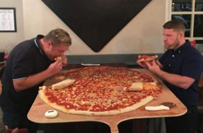 Dwóch mężczyzn z gigantyczną pizzą