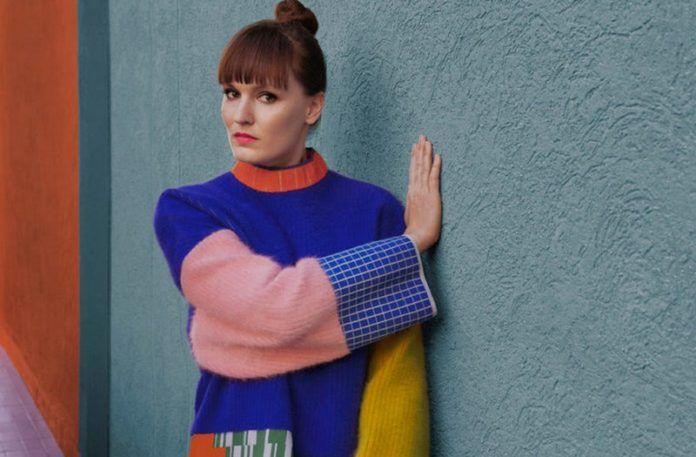 Młoda kobieta stoi bokiem na tle niebieskiego budynku