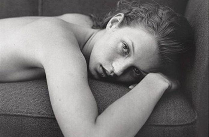 Czarno-białe zdjęcie młodej kobiety leżącej na łózku