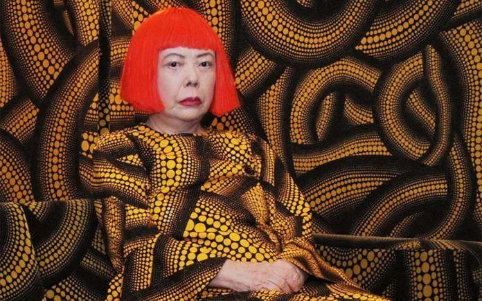 na zdjęciu znajduje się kobieta z czerwonymi włosami. Jej sukienka oraz tło są czarne w żółte wzory