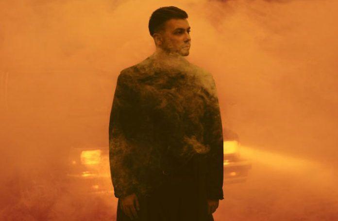 Mężczyzna w płaszczu na tle pomarańczowej mgły