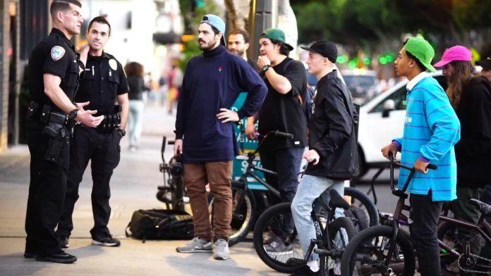 grupa skejtów na bmx'ach rozmawia z policjantami