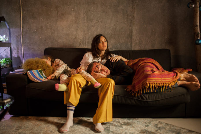 Dziewczyna w żółtych spodniach siedząca na kanapie, na niej leży mężczyzna