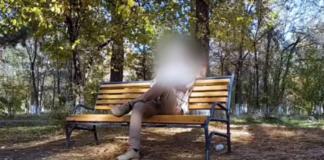 Mężczyzna siedzący na ławce z zakrytą twarzą