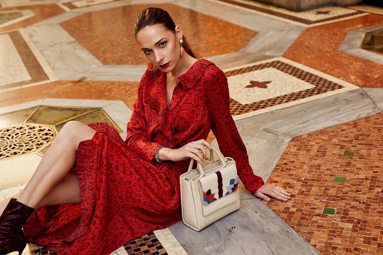 Na zdjeciu widzimy mloda kobieta ubrana w czerwona sukienke z bezowa wzorzysta torebka siedzi ona na kolorowym okazalym dywanie