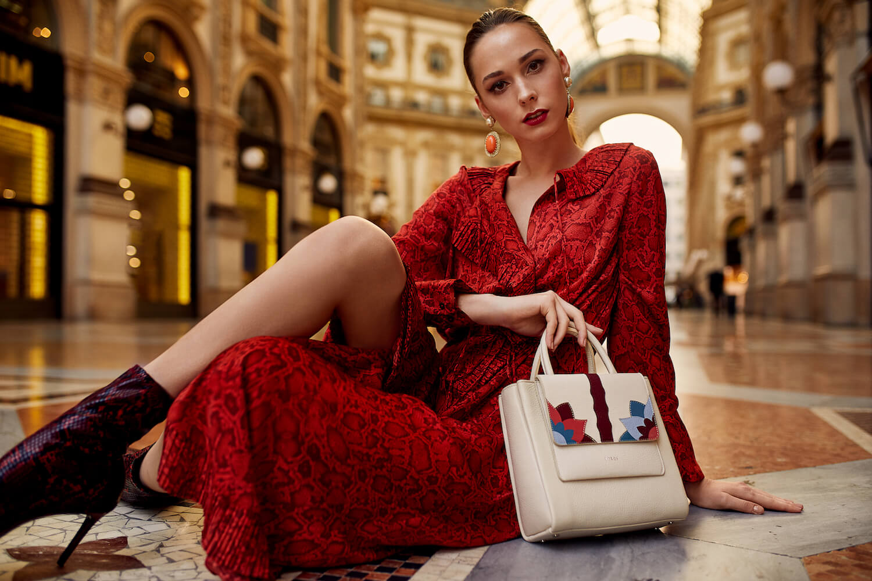 Na zdjeciu widzimy mloda kobiete ubrana w czerwona elegancka sukienke siadzaca w bogatym pomieszeniu z bezowa torba
