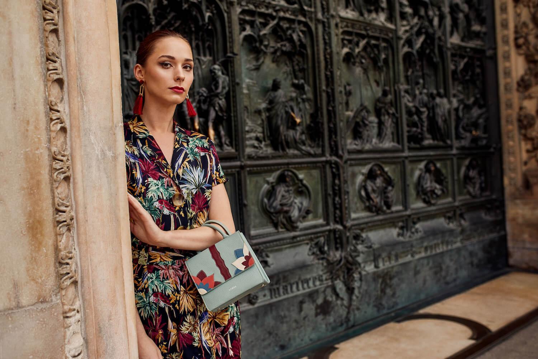 Na zdjeciu widzimy mloda elegancka kobiete opierajaca sie o filar w tle widzimy okazala czarna kamienice