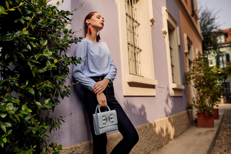 Na zdjeciu widzimy mloda kobiete z niebieska torebka opierajaca sie o fioletowa kamienice