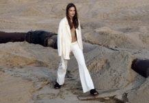 Dziewczyna ubrana na biało idąca przez piaszczysty teren